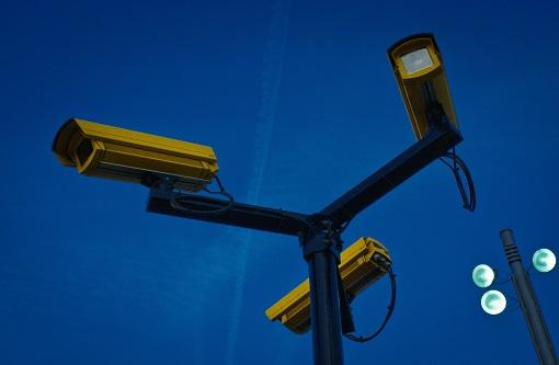 Három elemű póznára szerelt sárga színű kültéri kamerarendszer.
